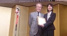長岡技術科学大学の新原学長(写真左)より優秀ポスター賞の表彰をうける笹本さん(写真右)